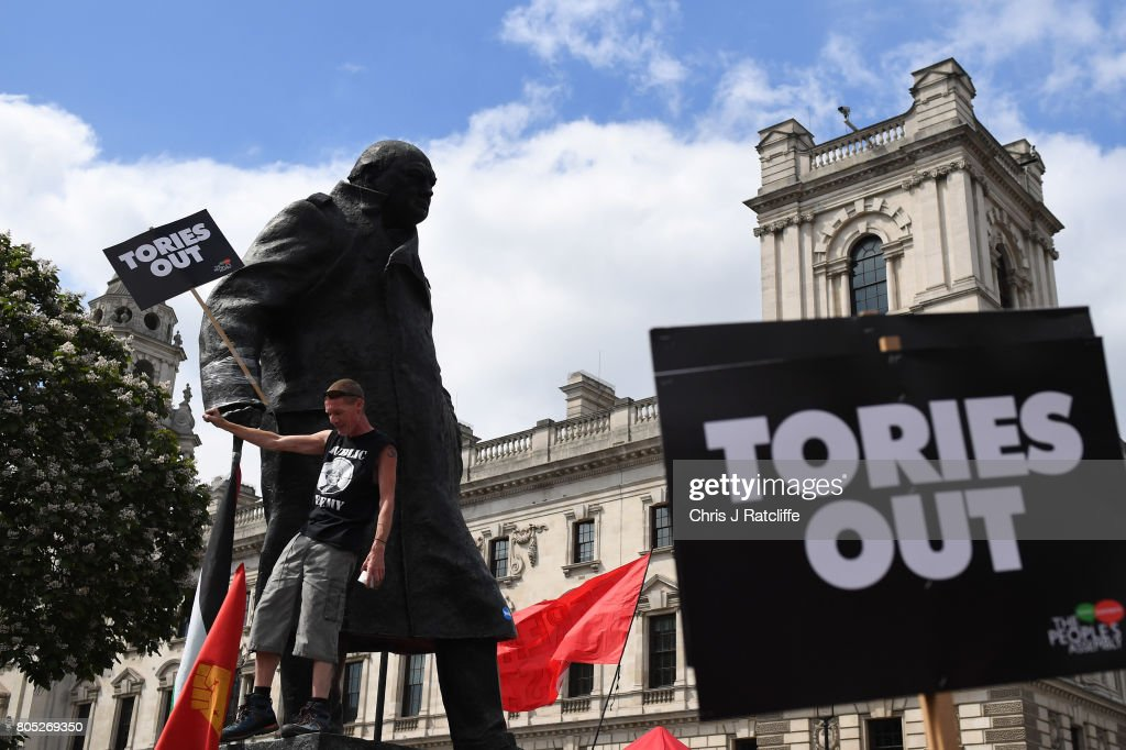 A demonstrator climbs the Statue of Winston Churchill as he waits for Labour Party leader, Jeremy Corbyn to speak during the 'Not One Day More' march at Parliament Square on July 1, 2017 in London, England. Thousands of protesters joined the anti-Tory demonstration at BBC Broadcasting House and marched to Parliament Square. The demonstrators were calling for an end to the Conservative Government and policies of austerity.