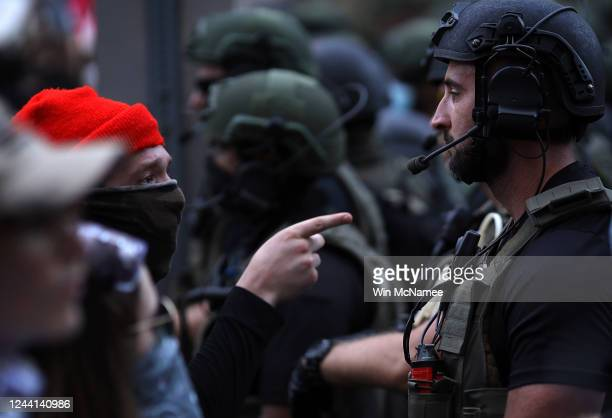 A demonstrator confronts a law enforcement officer dressed in riot gear near the White House during a peaceful protest against police brutality and...