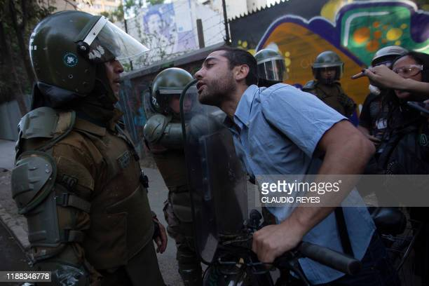 A demonstrator confronts riot police during a protest against President Sebastian Pinera's government in Santiago on December 13 2019 Chilean police...