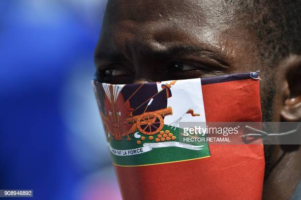 A demonstrator cover his face with a Haitian flag in PortauPrince on January 22 during a protest against the disparaging comments made by US...