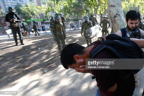 A demonstrator covers his eyes after being sprayed pepper gas by the police during protests against president Piñera at Plaza Italia ona on December...