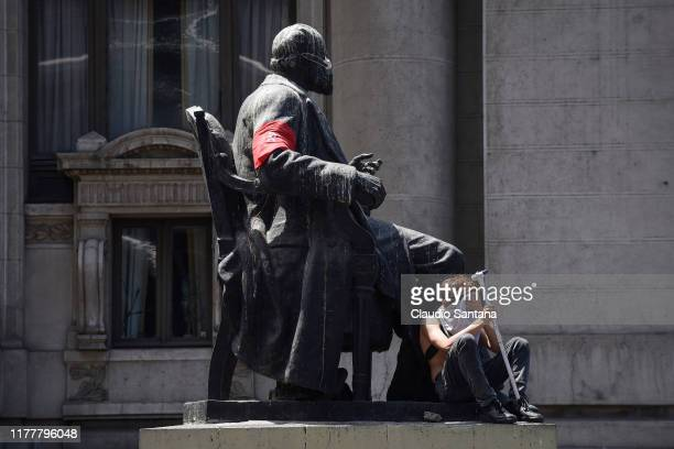 A demonstrator covers his face and rests during the sixth day of protests against President Sebastian Piñera on October 23 2019 in Santiago Chile...