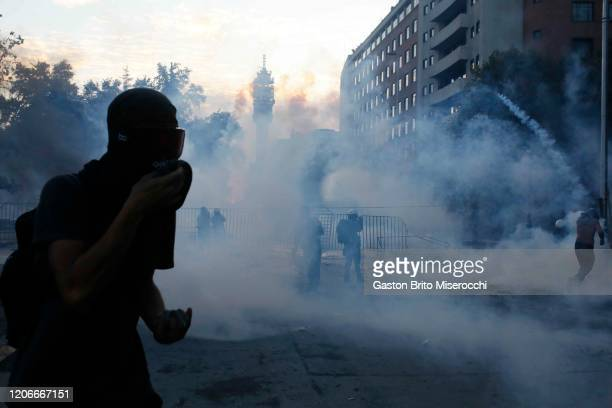 A demonstrator covers his face from the tear gas thrown by riot police during protests against the government of Sebastián Piñera on its second...
