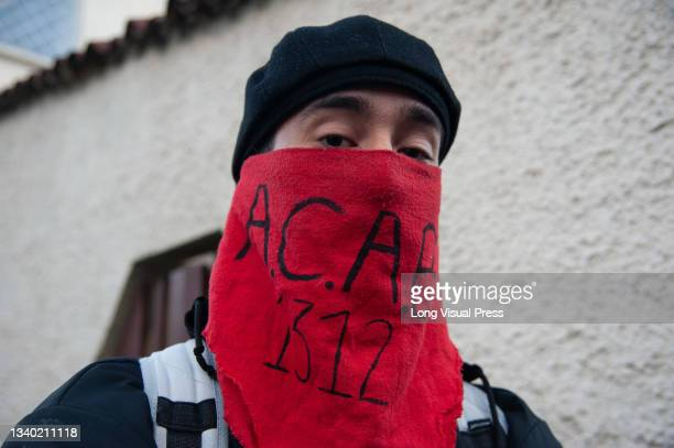 Demonstrator covers his face with a red scarf that reads the acronym 'A.C.A.B 1312' at the Villa Luz CAI police station were police officers tortured...