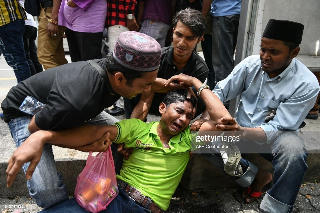 A demonstrator (C) cries during a protest against the persecution of Muslim ethnic minority Rohingya in Myanmar, in Kuala Lumpur on August 30, 2017. Hundreds of protesters from Myanmar demonstrated in Malaysia on August 30 against renewed violence in their homeland that has forced thousands of members of the Muslim ethnic minority Rohingya to flee. /