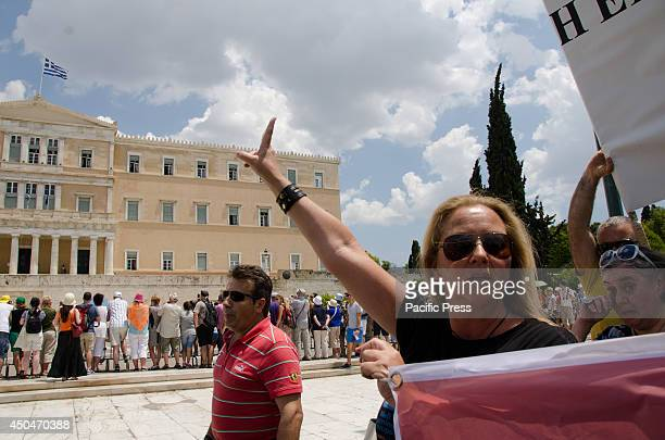 Demonstrator curses the Greek parliament with a 'mountza' . The rally was organized by unions and marked one year since the sudden closure of state...