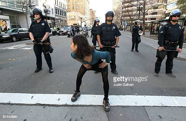 A demonstrator dances in front of Oakland police officers in riot gear as they monitor demonstrators during a national day of action against school...