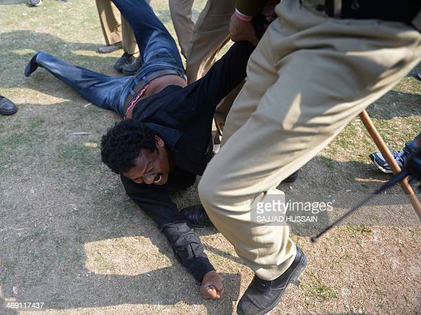 A demonstrator demanding a separate state of Telangana is detained by Indian policemen outside the parliament building in New Delhi on February 13...