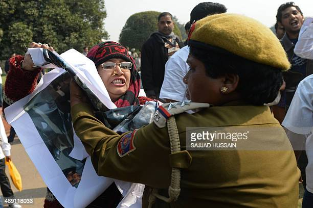 A demonstrator demanding a separate state of Telangana reacts while detained by an Indian policewoman outside the parliament building in New Delhi on...