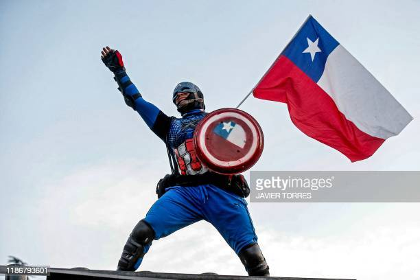 TOPSHOT A demonstrator disguised as Captain America holds a Chilean national flag during a protest against the government of Chilean President...