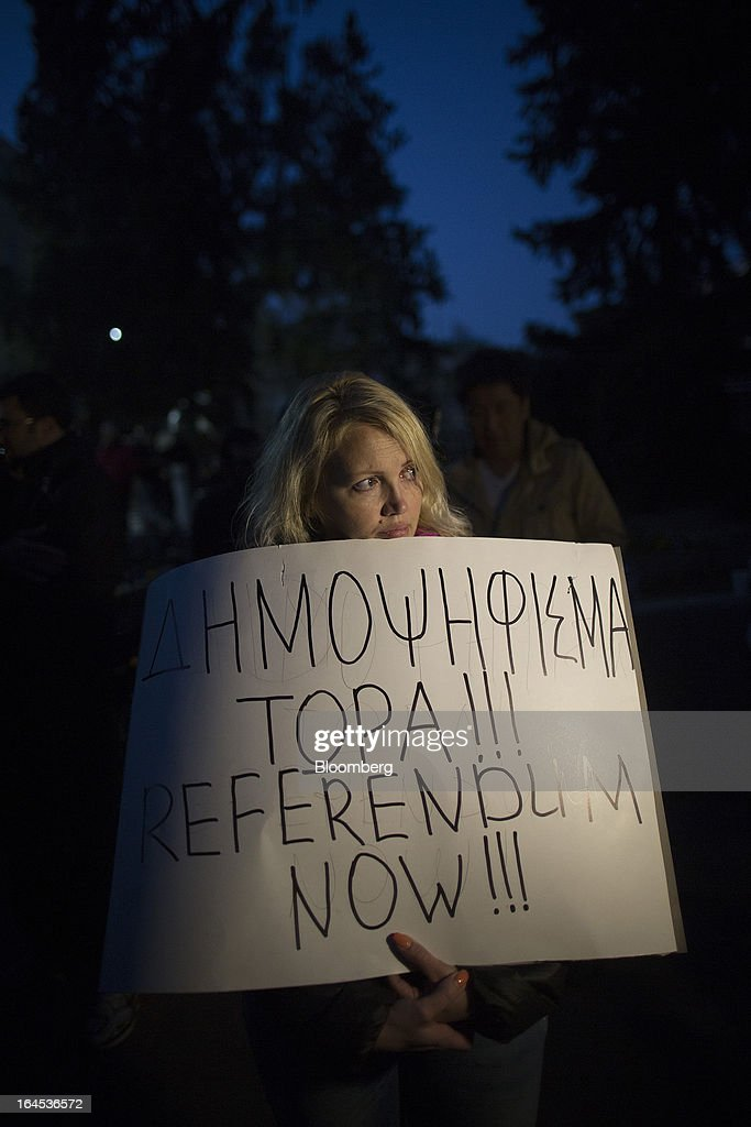 A demonstrator displays a banner calling for a referendum during a demonstration outside the Cypriot parliament in Nicosia, Cyprus, on Sunday, March 24, 2013. Cyprus's fate hangs in the balance as euro-area finance ministers meet today to decide whether the tiny Mediterranean island has done enough for a bailout that will avert its financial collapse. Photographer: Simon Dawson/Bloomberg via Getty Images