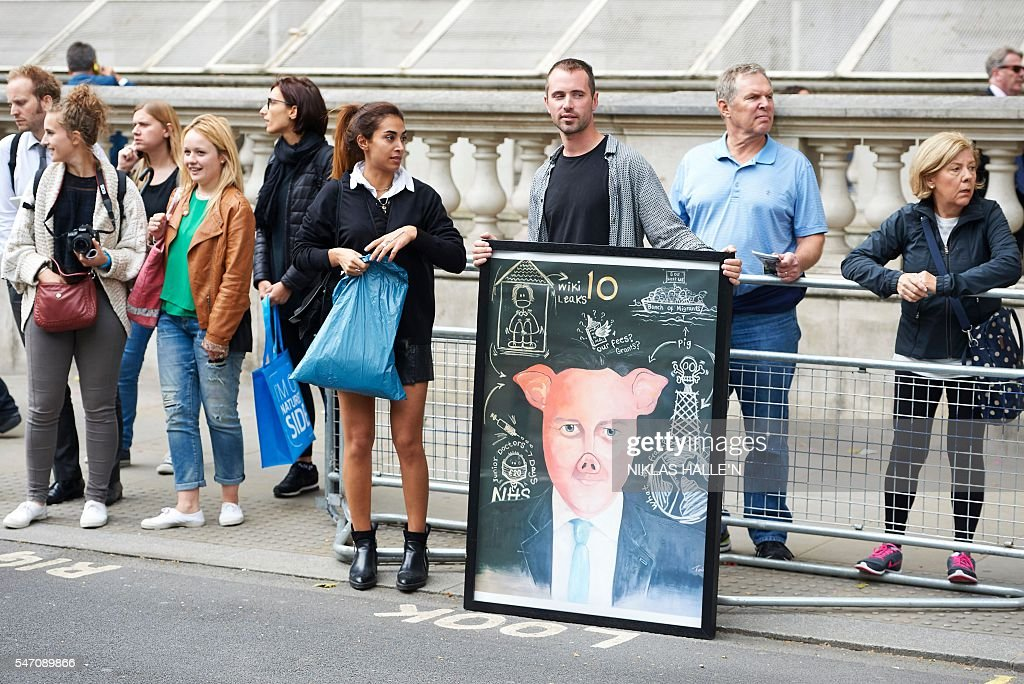 A demonstrator displays a painting depicting former British Prime minister David Cameron in central London on July 13, 2016, on the day new British Prime Minister Theresa May takes over at number 10. Theresa May took office as Britain's second female prime minister on July 13 charged with guiding the UK out of the European Union after a deeply devisive referendum campaign ended with Britain voting to leave and David Cameron resigning. / AFP / NIKLAS HALLE'N