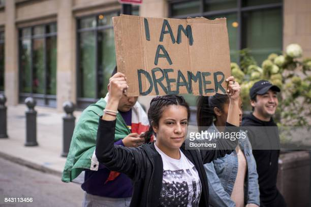 A demonstrator displays a placard as she marches in front of the US Immigration and Customs Enforcement headquarters while protesting the end of the...