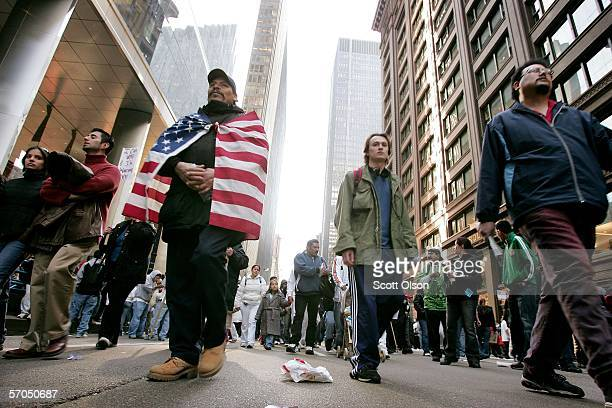 A demonstrator draped in an American flag leaves a rally at the Federal Building Plaza thousands joined together to protest house bill HR4437 which...