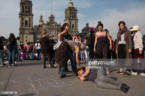 A demonstrator draws an outline of a woman lying on the ground during a rally on International Women's Day in Mexico City Mexico on Friday March 8...