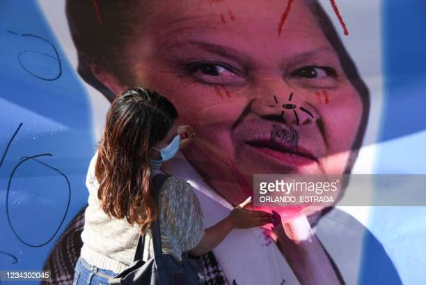 Demonstrator draws on a banner with a photograph of Guatemala's Attorney General Consuelo Porras during a protest demanding the resignation of...