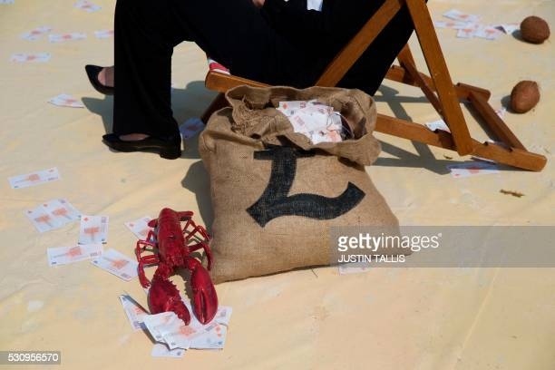 """Demonstrator dressed as a businessman protests against tax avoidance at a """"tropical 'tax' haven"""" in central London on May 12 near the venue of the..."""