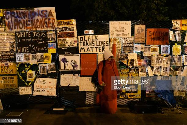 Image contains profanity.) A demonstrator dressed as a character from The Handmaid's Tale raises their fist in front of the fence surrounding...