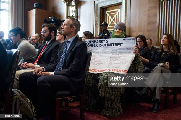 A demonstrator dressed as a swamp creature holds a sign as David Bernhardt President Donald Trumps nominee to be Interior Secretary testifies during...