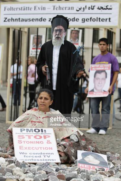Demonstrator dressed as a victim of a stoning execution and a man dressed as Iranian Supreme Leader Ayatollah Ali Khamenei join Iranian exiles...