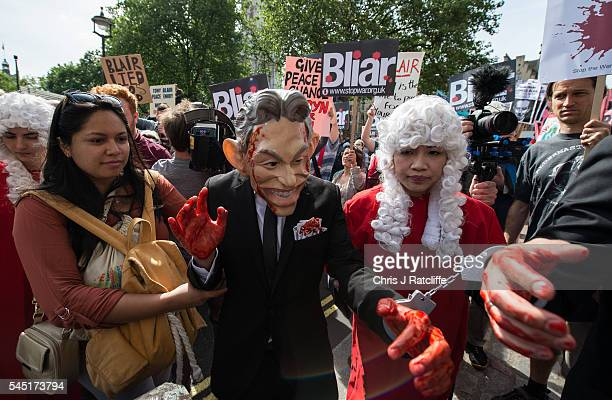 A demonstrator dressed as former British Prime Minister Tony Blair arrives with painted red hands and in hand cuffs outside the Queen Elizabeth II...