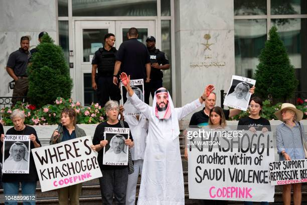 A demonstrator dressed as Saudi Arabian Crown Prince Mohammed bin Salman with blood on his hands protests with others outside the Saudi Embassy in...