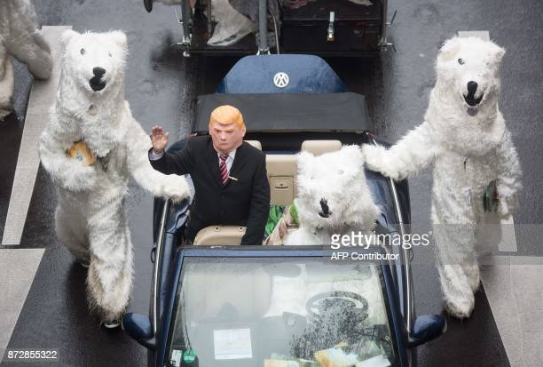 A demonstrator dressed as US President Donald Trump waves from a car as he parades with other activists dressed as polar bears during a protest of...