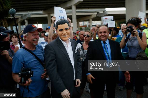 A demonstrator dressed in a Mitt Romney mask entertains the crowd as labor activists and protestors march against the candidacy of Romney on the...