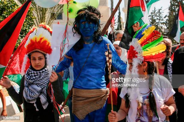 A demonstrator dressed in blue and wearing a string bow his shoulder as a character from James Cameron's Avatar franchise walks with other girls...