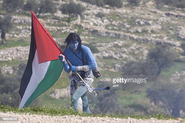 A demonstrator dressed like the Na'vi characters from the blockbuster film 'Avatar' carries a Palestinian flag through a haze of tear gas during the...