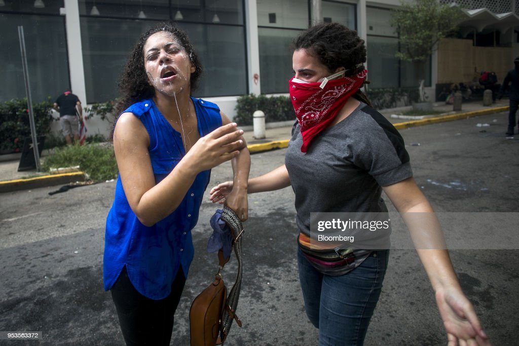 A demonstrator drips with milk after being pepper-sprayed during a protest against austerity measures in the Hato Rey neighborhood of San Juan, Puerto Rico, on Tuesday, May 1, 2018. Puerto Rico demonstrators battled police on San Juan's streets as they marched against proposed cuts to retirement benefits and looser labor laws as the bankrupt island seeks to reduce $74 billion of debt. Photographer: Xavier Garcia/Bloomberg via Getty Images