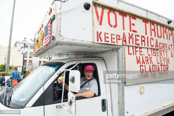 A demonstrator drives a vehicle displaying signs in support of US President Donald Trump outside of the Charleston Gaillard Center ahead of the...