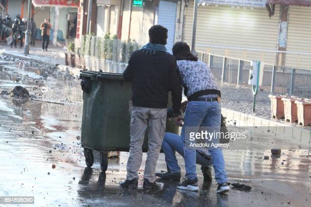Demonstrator duck behind a trash bin while they clash with riot police within antigovernment protests in Sulaymaniyah Iraq on December 18 2017...