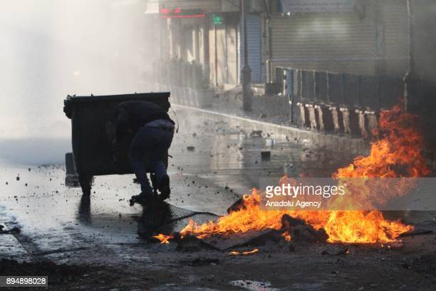 A demonstrator ducks behind a trash bin while they clash with riot police within antigovernment protests in Sulaymaniyah Iraq on December 18 2017...