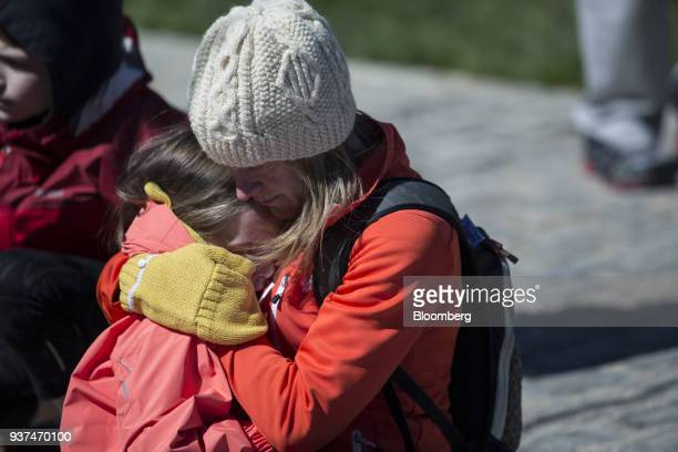 A demonstrator embraces a child on Pennsylvania Avenue during the March For Our Lives in Washington DC US on Saturday March 24 2018 Thousands of high...