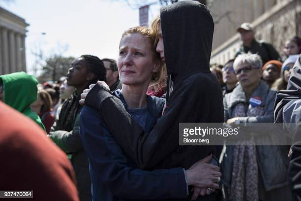 A demonstrator embraces a child while listening to speeches on Pennsylvania Avenue during the March For Our Lives in Washington DC US on Saturday...