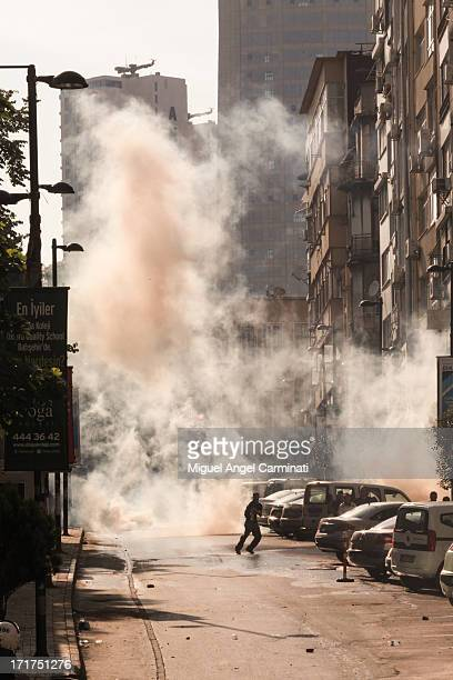 Demonstrator escaping from tear gas in Osmanbey area near Taksim Square during the riots at Istanbul.