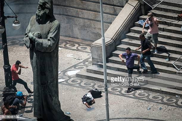 A demonstrator falls after a tear gas canister bursts a Rio de Janeiro state's public servants protest against austerity measures in front of the Rio...