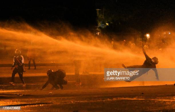 Demonstrator falls as they are hit by water cannon during clashes with riot police amid ongoing protests against the government of Colombian...