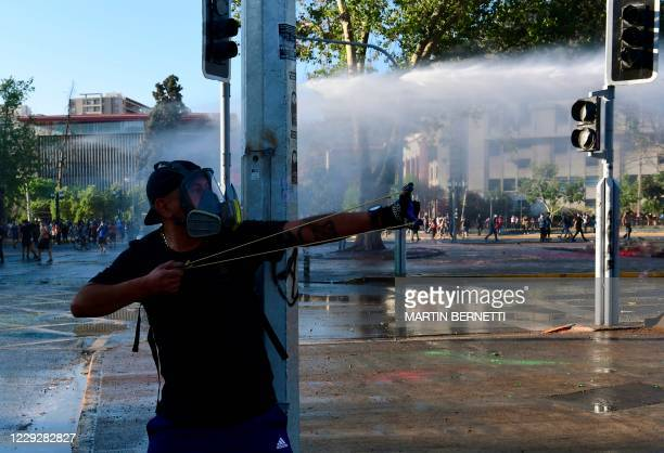 Demonstrator fires a slingshot towards riot police during a protest against Chilean President Sebastian Pinera's government on the constitutional...