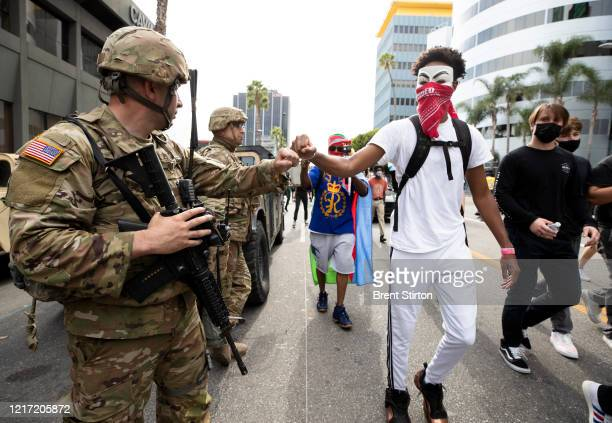 A demonstrator fist bumps a member of the National Guard during a march in response to George Floyd's death on June 2 2020 in Los Angeles California...