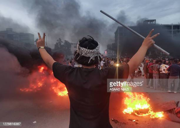 Demonstrator flashes V signs by burning tyres amid clashes between Iraqi anti-government protesters and supporters of firebrand Shiite cleric Moqtada...