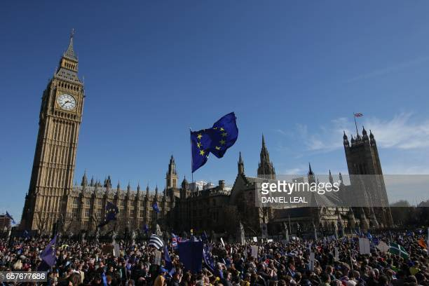 A demonstrator flies an EU flag outside the Houses of Parliament during a rally following an anti Brexit proEuropean Union march in London on March...