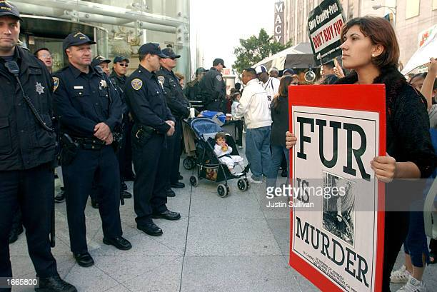 A demonstrator from the group In Defense of Animals holds a sign as police officers block the entrance to Neiman Markus November 29 2002 in San...