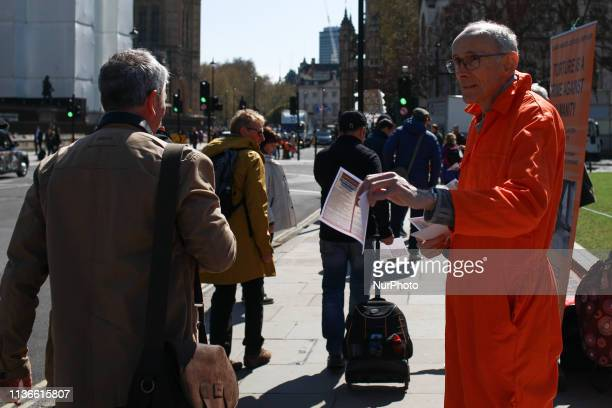 A demonstrator from the London Guantanamo Campaign wearing an orange prison jumpsuit hands out flyers outside the Houses of Parliament in London...