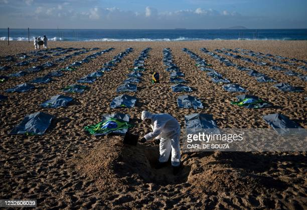 Demonstrator from the Rio de Paz human rights activist group digs a symbolic grave in front of rows of bags symbolizing bodybags on Copacabana beach,...