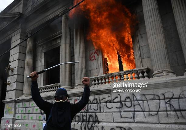 Demonstrator gestures after setting on fire an office of the Congress building during a protest demanding the resignation of President Alejandro...
