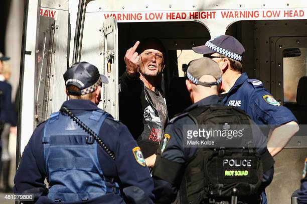 A demonstrator gestures at the media as he is detained by police after a disturbance as the 'Reclaim Australia' rally and counter rally protesters...