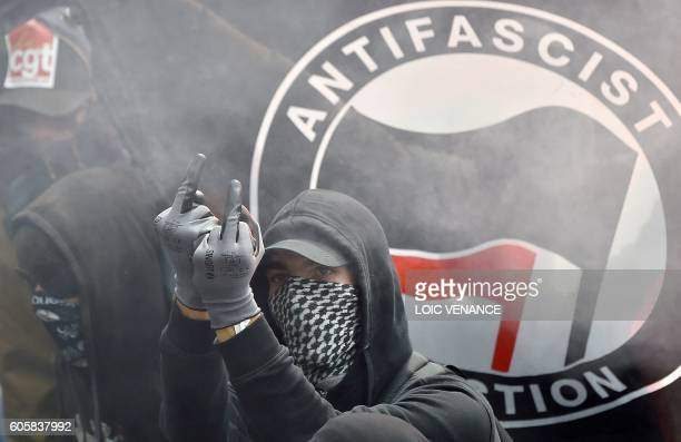 Demonstrator gestures in front of an Antifascist Action flag during a demonstration against the controversial labour reforms of the French government...