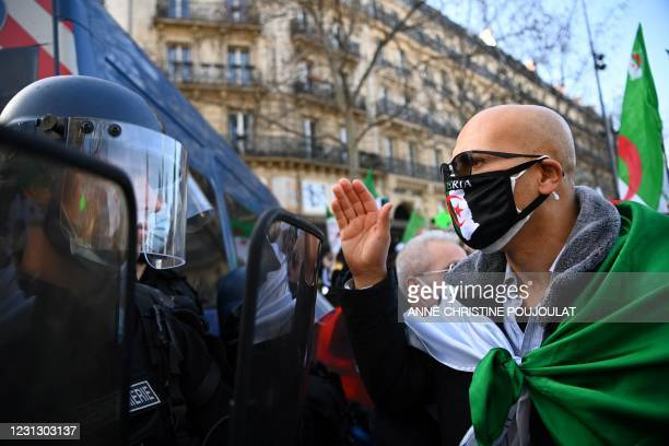 Demonstrator gestures in front of French gendarmes during a rally in Paris on February 21 in support of the Hirak anti-government movement in...